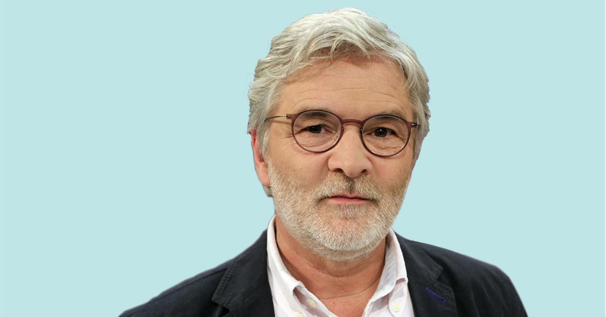 Dr. Martin Terhardt schmunzelt vor blauem Hintergrund.
