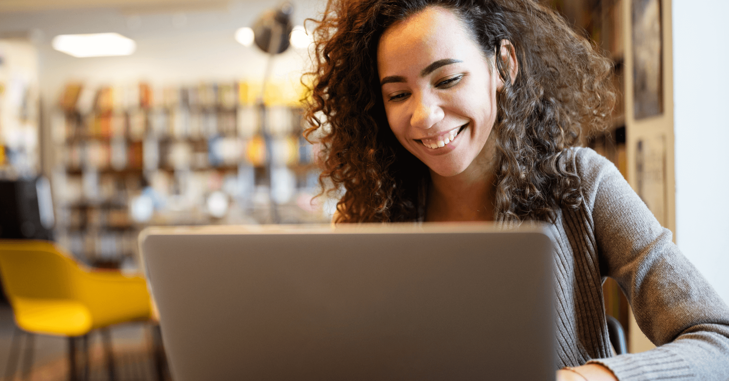 A young woman smiles while looking at her laptop computer.