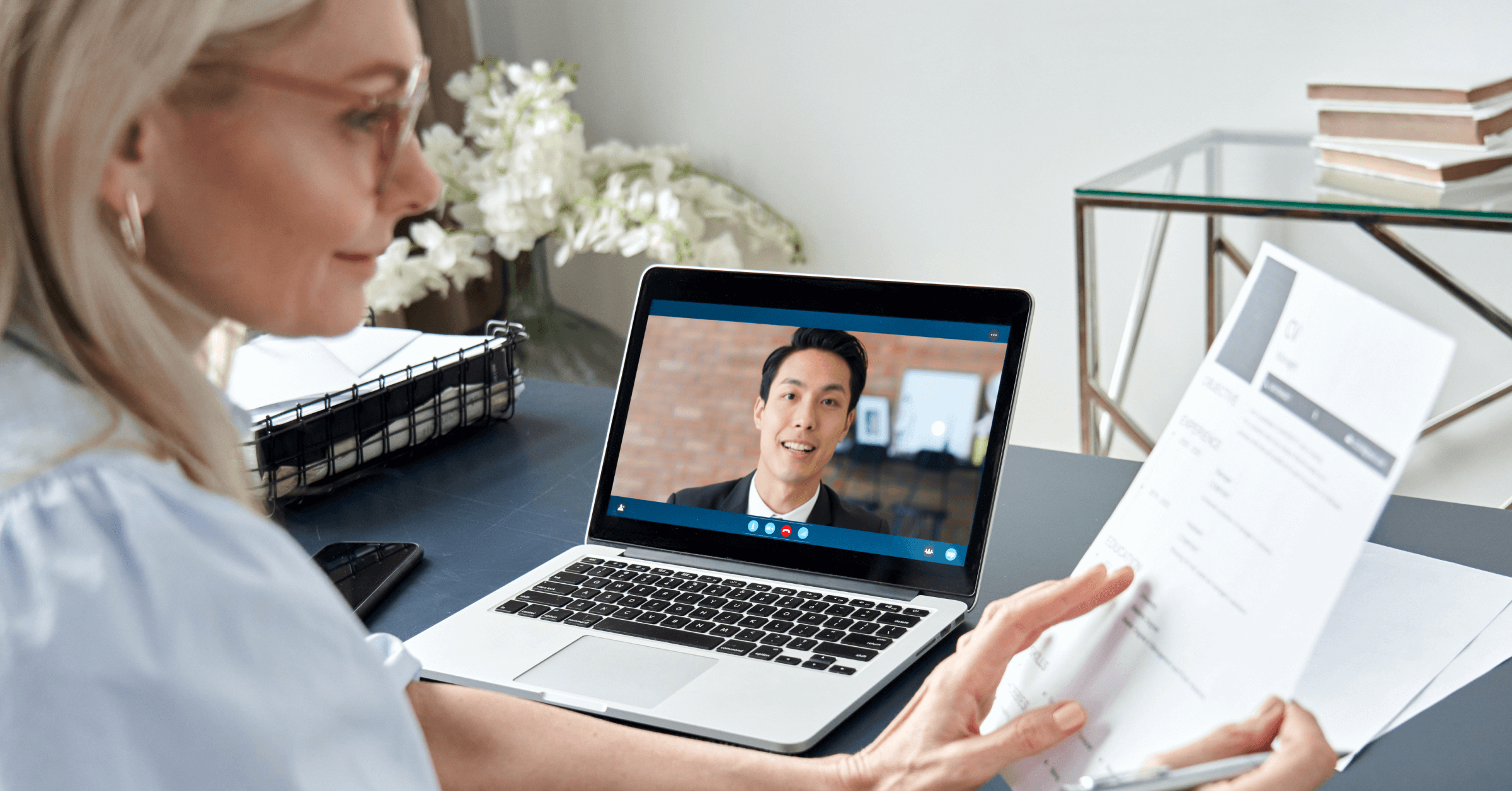 A woman conducting a virtual interview with a residency applicant.