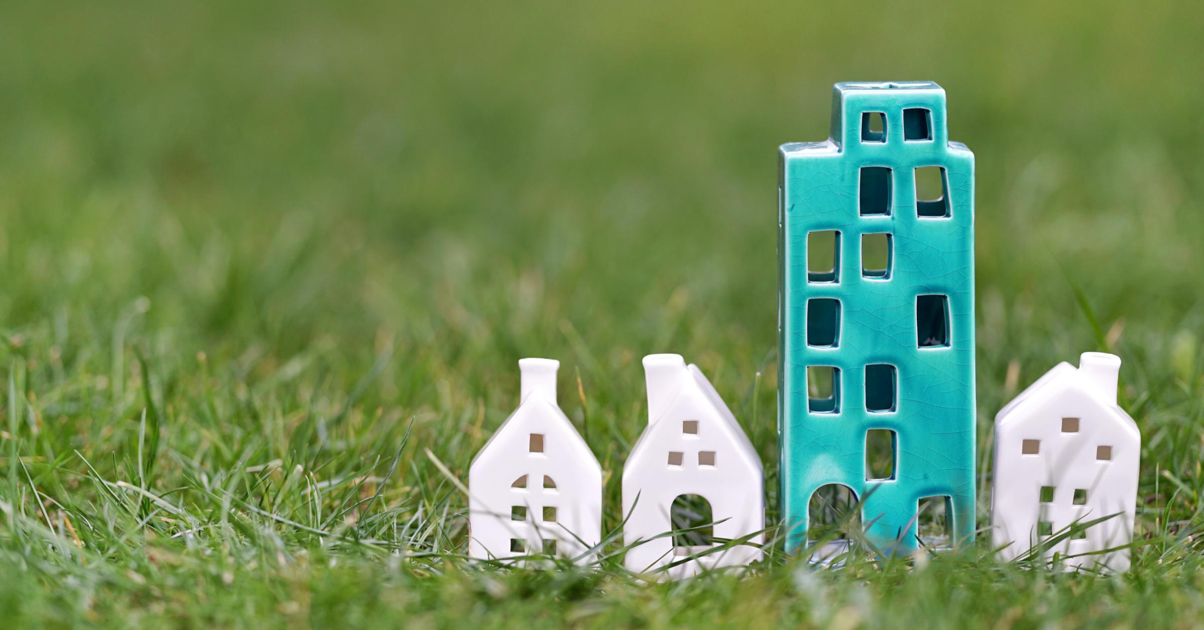 Ein blaues Keramikhaus steht inmitten dreier kleinerer weißer Keramikhäuser auf einer Wiese.