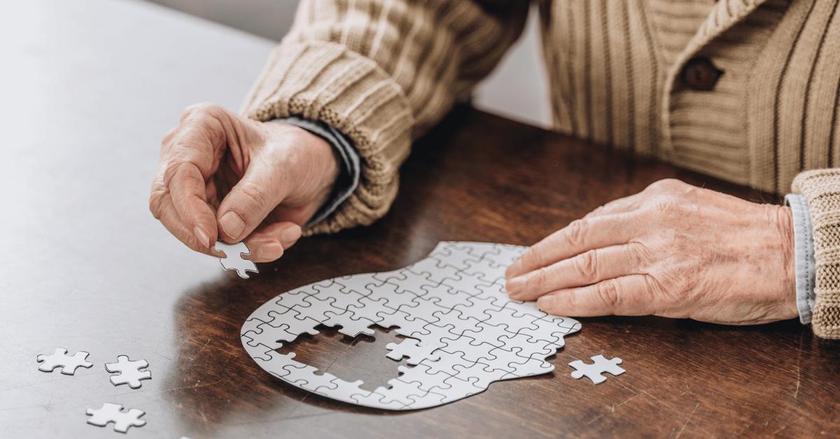 Eine alte Hand puzzelt einen Kopf zusammen.