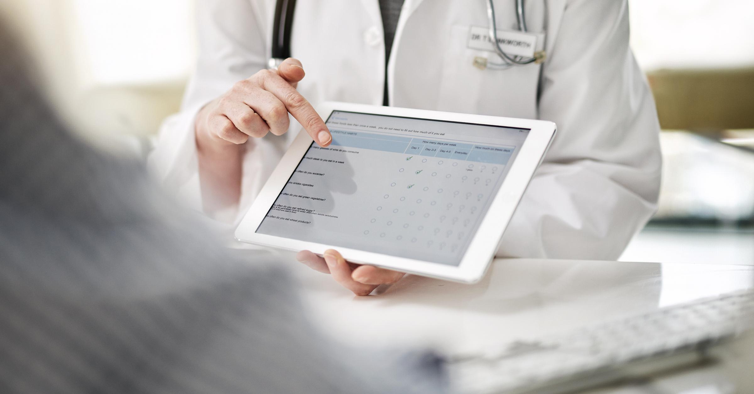 Eine Ärztin zeigt einem Patienten einen Fragebogen auf einem Tablet.